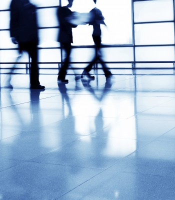 Businesspeople walking in modern interior, blurred motion.